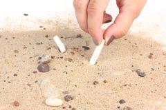 Mettendo sigaretta in sabbia sul fondo bianco Immagine Stock Libera da Diritti