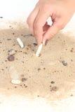 Mettendo sigaretta in sabbia sul fondo bianco Immagini Stock