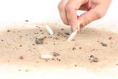 Mettendo sigaretta in sabbia sul fondo bianco Fotografia Stock Libera da Diritti