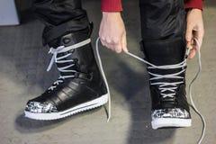 Mettendo sugli stivali dello snowboard Fotografie Stock