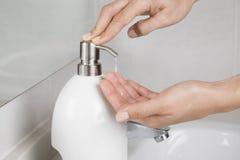 Mettendo un certo sapone sulle mani Immagine Stock
