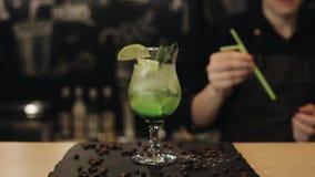 Mettendo una paglia verde nel cocktail di mojito archivi video