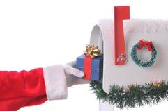 Mettere del Babbo Natale presente nella cassetta postale Fotografia Stock