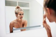 Mettere femminile sull'idratante sulla sua pelle facciale Fotografie Stock Libere da Diritti