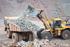 Mettez à la terre le camion de déchargeur de chargement de moteur avec des roches dans la carrière photographie stock libre de droits