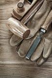 Mettez en bloc le marteau rasant les gants protecteurs de burin plat sur le boa en bois photo libre de droits