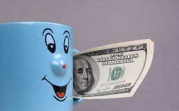 Mettez en forme de tasse avec l'argent des dollars dans la main Photographie stock libre de droits