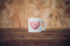Mettez en forme de tasse la forme de coeur sur le plancher en bois dans le jour du ` s de Valentine Images libres de droits
