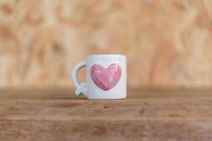 Mettez en forme de tasse la forme de coeur sur le plancher en bois dans le jour du ` s de Valentine Photos stock