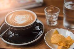 Mettez en forme de tasse le café et placez la nourriture et buvez sur la table en bois dans le café au matin Photo libre de droits