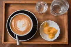 Mettez en forme de tasse le café et placez la nourriture et buvez sur la table en bois dans le café au matin Images stock