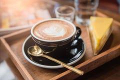 Mettez en forme de tasse le café et placez la nourriture et buvez sur la table en bois dans le café au matin Photo stock