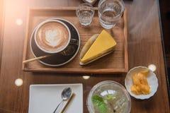 Mettez en forme de tasse le café et placez la nourriture et buvez sur la table en bois dans le café au matin Image libre de droits