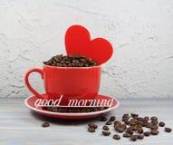 Mettez en forme de tasse le rouge avec les graines de café, le coeur et bonjour d'inscription Images libres de droits