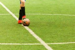 Mettez en place le joueur en avant avec une boule dans le terrain de football central Photo libre de droits