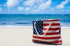 Mettez en sac avec des couleurs de drapeau américain près de l'océan sur la plage sablonneuse Photos stock