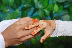Mettez l'anneau de mariage sur le doigt Photographie stock