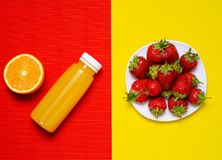 Mettez la fraise en bouteille de jus d'orange sur le fond de jaune orange Photographie stock libre de droits
