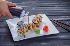 Mettez la sauce en bouteille de versement sur des sushi Bouteille de compression dans la main du ` s de l'homme Le Japon envoie d Photos libres de droits