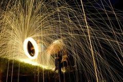 Mettez le feu à POI, la laine en acier flamboyante tournant, femme avec le parapluie Photographie stock libre de droits