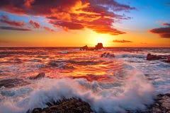 Mettez le feu au ciel et aux vagues se brisant au-dessus des roches dans le Laguna Beach, CA Photo stock