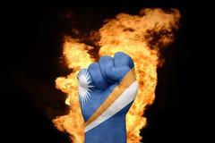 Mettez le feu au poing avec le drapeau national de Marshall Islands Photos libres de droits
