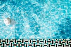 Mettez le flotteur en commun, anneau flottant dans une piscine bleue régénératrice avec des ombres de feuille de palmier dans l'e Photo libre de droits