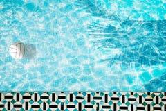 Mettez le flotteur en commun, anneau flottant dans une piscine bleue régénératrice avec des ombres de feuille de palmier dans l'e Image stock