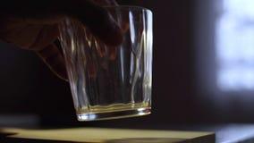 Mettez le verre sur le conseil en bois sur la table banque de vidéos