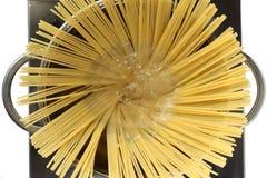 Mettez les spaghetti dans l'eau bouillante photos stock