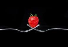 Mettez une fraise sur 2 fourchettes Photographie stock