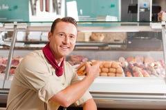 Metzger, der auf Frischfleisch für den Verkauf zeigt Stockfotografie