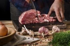 Metzger, der Schweinefleisch auf hölzernem Brett auf einem Holztisch auf dem dunklen Hintergrund schneidet stockbilder