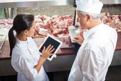 Metzger, die Digital-Tablet im Speicher verwenden Stockbilder