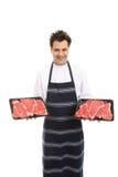Metzger mit Tellersegmenten des Steaks Lizenzfreies Stockfoto