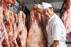 Metzger Standing By Meat, das im Schlachthaus hängt Lizenzfreie Stockfotos