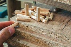 Meubilairmontage, houten pennen, bevestigingsmiddelverbinding op spaanplaatwerkstukken, close-up stock foto's