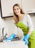 Meubles de nettoyage de femme au foyer dans la cuisine Photographie stock libre de droits