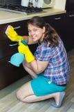 Meubles de nettoyage de jeune fille dans la cuisine photographie stock libre de droits