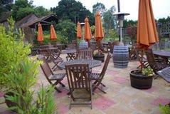 Meubles de patio des parapluies, des chaises en bois, et des tables en bois Image libre de droits