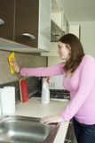 Meubles de polissage de fille attirante sur la cuisine Photos stock