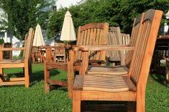 Meubles et parapluies en bois bien usés sur la pelouse manicured Photographie stock libre de droits