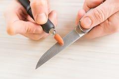 Meulage d'un vieux couteau avec la meule rotatoire Photos libres de droits