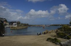 Mevagissey Harbour and View of St. Austell Beach in Cornwall. During incoming tide Royalty Free Stock Photos