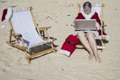 Mevr. Claus die aan laptop computer op zandig strand werken stock foto's