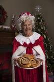 Mevr. Claus die verse gebakken kaneelbroodjes houden Stock Foto