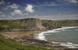 Mewslade Bay, Gower Peninsula. View of Mewslade Bay with cloudy blue sky and rocky cliffs Royalty Free Stock Photos