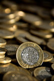 Mexicaans 10 peso'smuntstuk in de voorgrond, met veel meer muntstukken op de achtergrond Stock Foto's