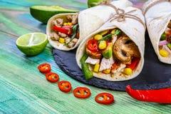 Mexicaans restaurant snel voedsel - verpakte burritos met varkensvleesvlees, paddestoelen en groentenclose-up bij houten bureau M stock foto's
