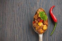 Mexicaans schotelchili con carne in een lepel op een houten achtergrond Stock Foto's